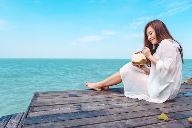 Mulher bebendo suco de coco à beira-mar