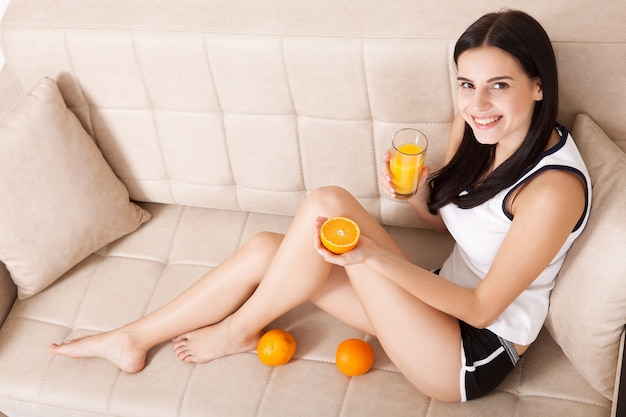 Mulher bebendo suco de laranja em casa