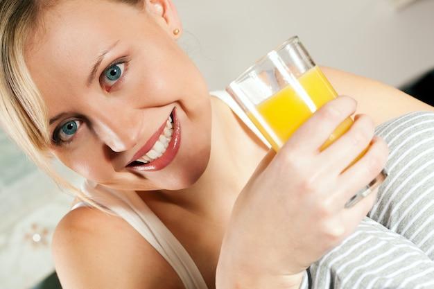 Mulher bebendo suco de laranja