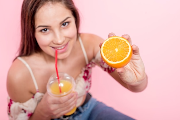 Mulher, bebendo, suco, e, segurando, cortado, laranja