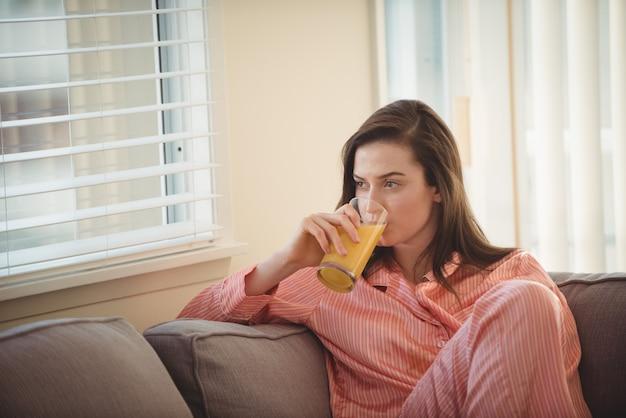 Mulher bebendo suco enquanto olha pela janela