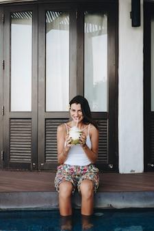 Mulher, bebendo, um, coco fresco
