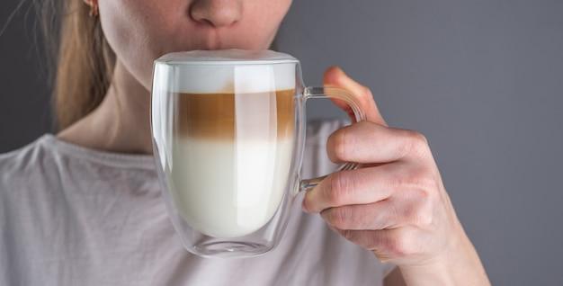 Mulher bebendo um delicioso café com leite fresco servido em um copo transparente com vidro duplo