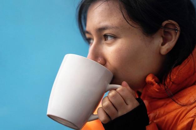 Mulher bebendo uma bebida quente