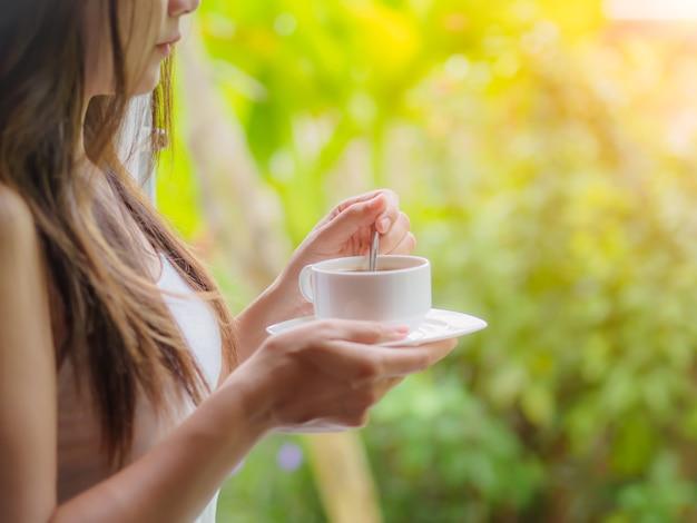 Mulher bebendo uma xícara de café no jardim da manhã