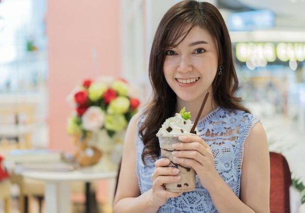 Mulher bebendo uma xícara de leite com chocolate no café
