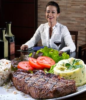 Mulher bebendo vinho tinto e comendo bife grelhado com purê de batata e salada