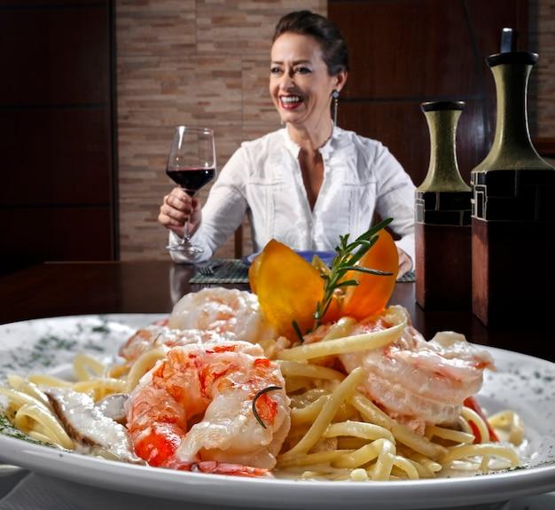 Mulher bebendo vinho tinto e comendo macarrão com camarão
