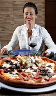 Mulher bebendo vinho tinto e comendo pizza