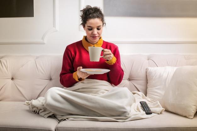 Mulher beber chá em casa