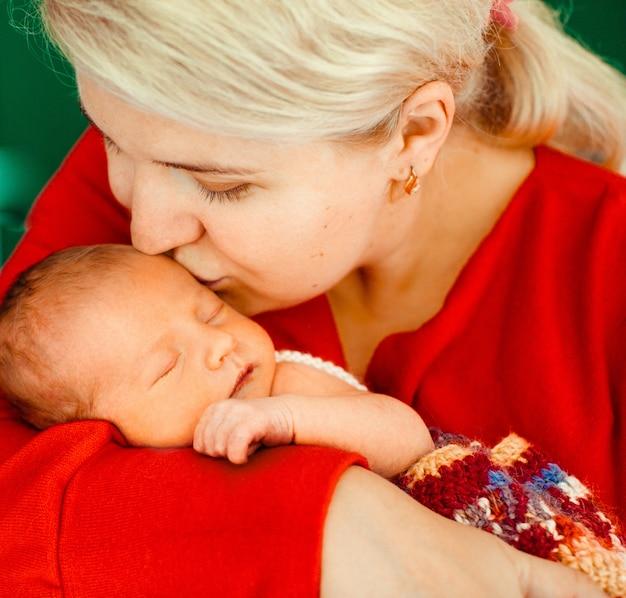Mulher beija terno recém nascido em seus braços