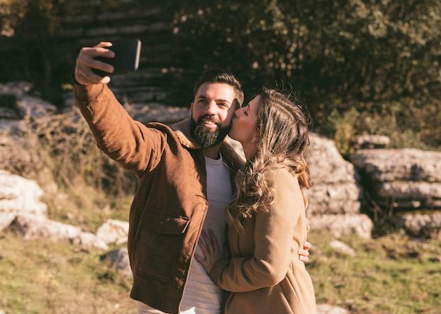 Mulher beijando o namorado enquanto ele tira uma selfie
