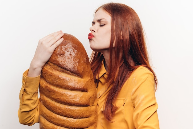Mulher beijando pão em fundo claro e camisa amarela produto de farinha vista recortada