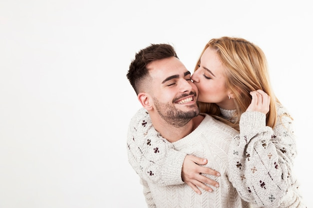 Mulher beijando sorrindo homem