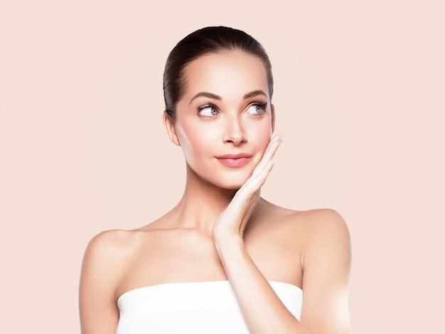 Mulher beleza rosto pele saudável maquiagem natural bela jovem modelo com as mãos. em bege.