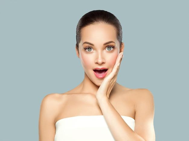 Mulher beleza rosto pele saudável maquiagem natural bela jovem modelo com as mãos. em cinza.