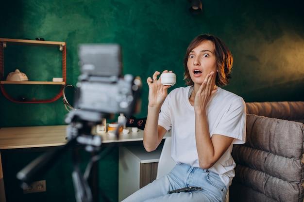 Mulher beleza vlogger filmando vlog sobre cremes