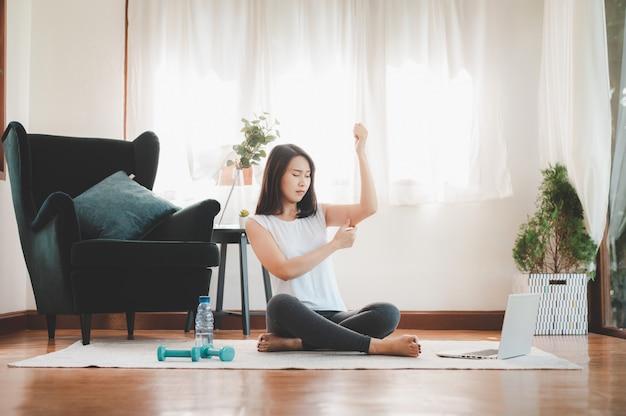 Mulher beliscar a pele flácida gorda do tríceps de braço antes de iniciar o exercício