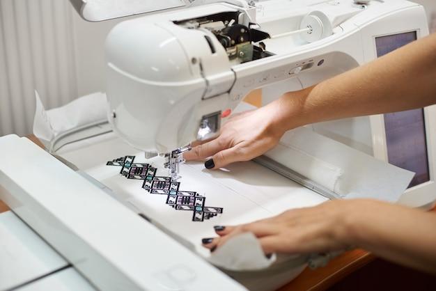 Mulher bem cuidada com as mãos trabalhando na máquina de costura, criando um padrão geométrico colorido