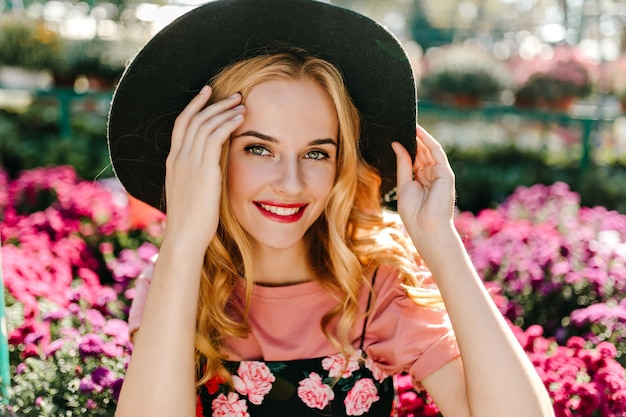 Mulher bem humorada com olhos grandes, posando no jardim. mulher jocund em pé de chapéu em flores cor de rosa.