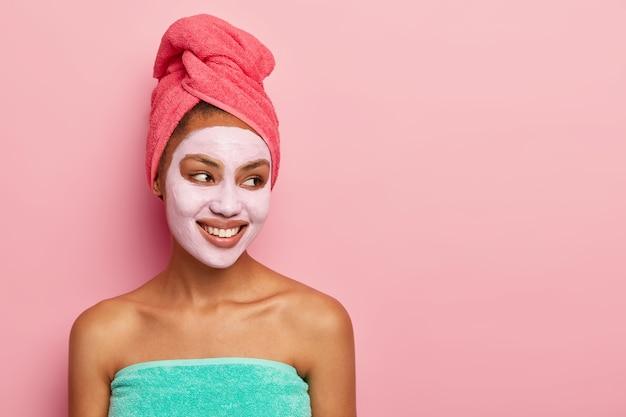 Mulher bem relaxada enrolada em uma toalha, aplica máscara de argila para reduzir linhas finas no rosto, olha alegremente de lado, posa contra a parede rosa