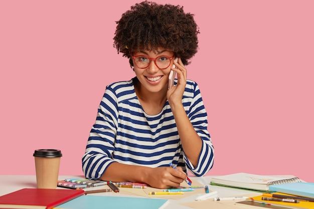 Mulher bem-sucedida de pele escura com corte de cabelo afro, vestida com roupas listradas, conversa agradável ao telefone enquanto desenha algo no bloco de notas, toma café para viagem, sente-se satisfeita e inspirada
