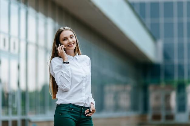 Mulher bem-sucedida falando ao telefone ao ar livre de um prédio de escritórios