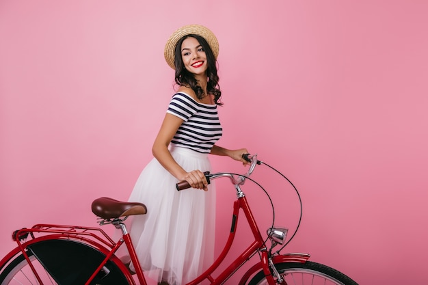 Mulher bem torneada inspirada em pé com uma bicicleta e desviar o olhar. feliz garota de cabelos castanhos com chapéu, aproveitando a sessão de fotos interna.