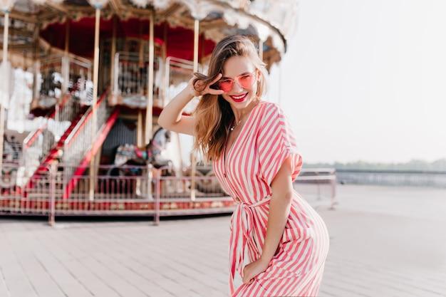 Mulher bem torneada posando perto de carrossel com sorriso inspirado. espectacular garota branca em vestido listrado, aproveitando o fim de semana no parque de diversões.