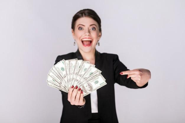 Mulher bem vestida, apontando o dedo em dinheiro, dólar. tiro do estúdio, interior. isolado em fundo cinza