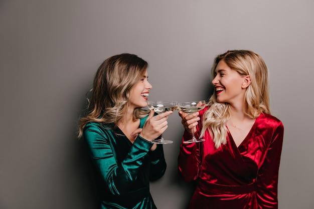 Mulher bem vestida de cabelos louros, olhando para a irmã com um sorriso e bebendo vinho. amigos felizes, desfrutando de champanhe juntos.