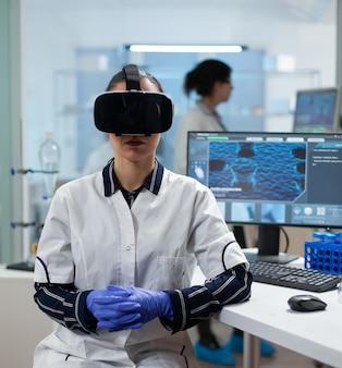 Mulher, bióloga cientista usando fone de ouvido de realidade virtual, analisando experiência em vacinas médicas