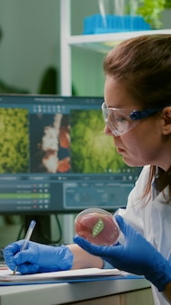 Mulher bióloga escrevendo perícia médica enquanto segura uma placa de petri com carne bovina vegana nas mãos, trabalhando no laboratório de microbiologia
