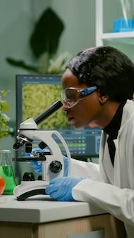 Mulher bióloga examinando lâmina biológica para perícia médica usando microscópio