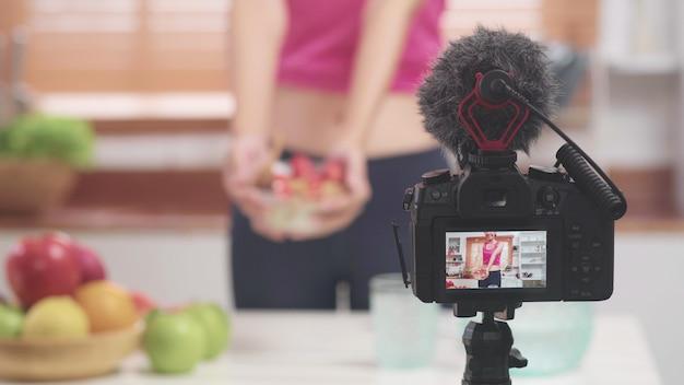 Mulher blogueira asiática fazer vlog como dieta e perda de peso, jovem fêmea usando gravação de câmera
