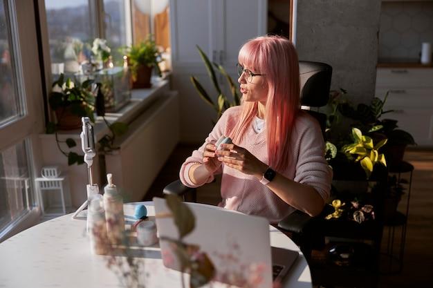 Mulher blogueira de beleza grava novo vídeo na mesa com produtos cosméticos e laptop