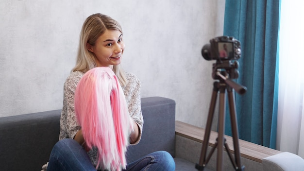 Mulher blogueira grava vídeo. ela fala sobre corte de cabelo e mostra uma peruca rosa. estilista e consultora de moda gravando a palestra