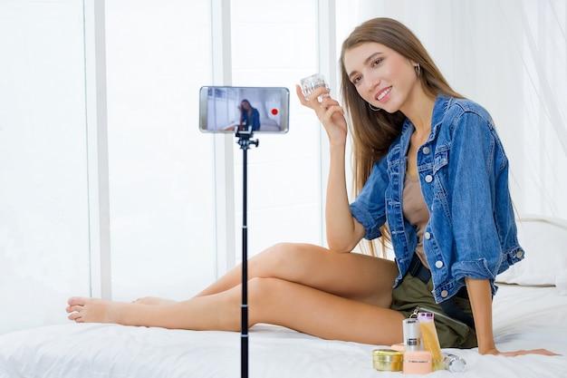 Mulher blogueiro está apresentando cosméticos de beleza e transmitindo vídeo ao vivo nas mídias sociais com tecnologia de smartphone