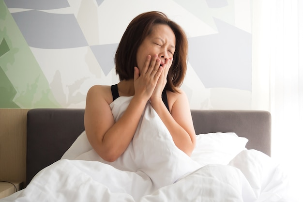 Mulher bocejando na cama