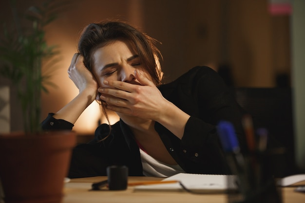 Mulher bocejando no escritório