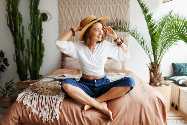 Mulher boêmia brincalhão posando no quarto elegante com interior incrível, palmeiras e macrame