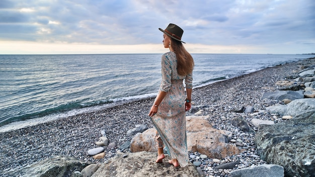 Mulher boho com vestido longo e chapéu de feltro