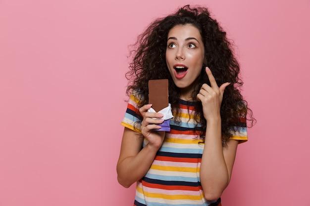 Mulher bonita 20 anos com cabelo encaracolado segurando uma barra de chocolate