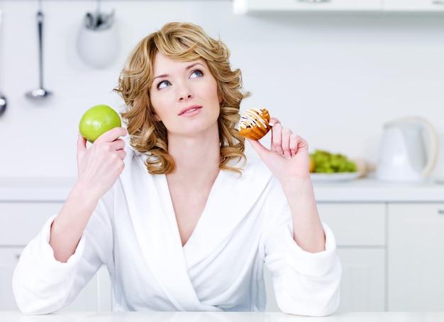 Mulher bonita a pensar escolhendo entre comida saudável e comida calórica - dentro de casa