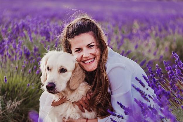 Mulher bonita, abraçando seu cachorro retriever dourado em campos de lavanda ao pôr do sol.
