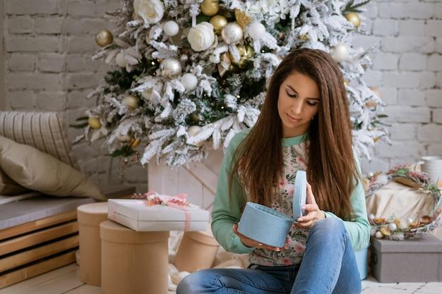 Mulher bonita abre presentes em casa na árvore de natal