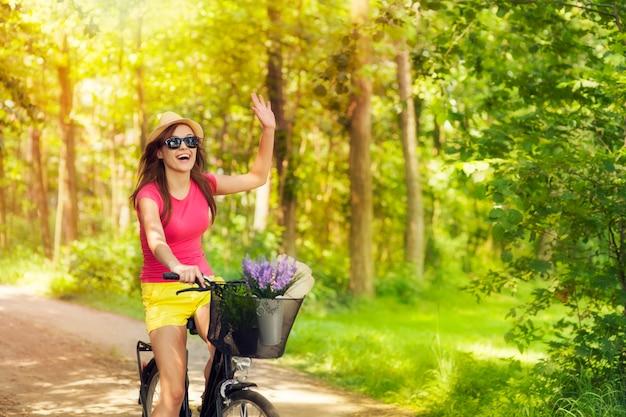Mulher bonita acenando para alguém durante o ciclismo