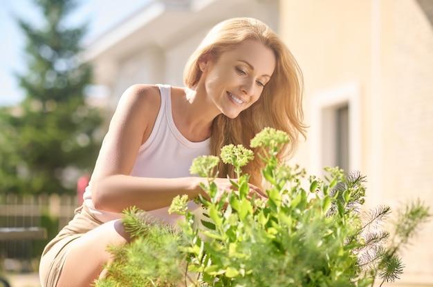 Mulher bonita admirando flores perto de casa