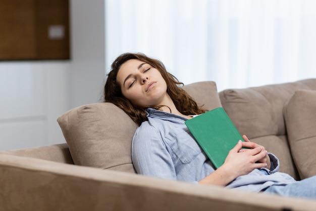 Mulher bonita adormeceu lendo um livro enquanto estava deitada no sofá em casa