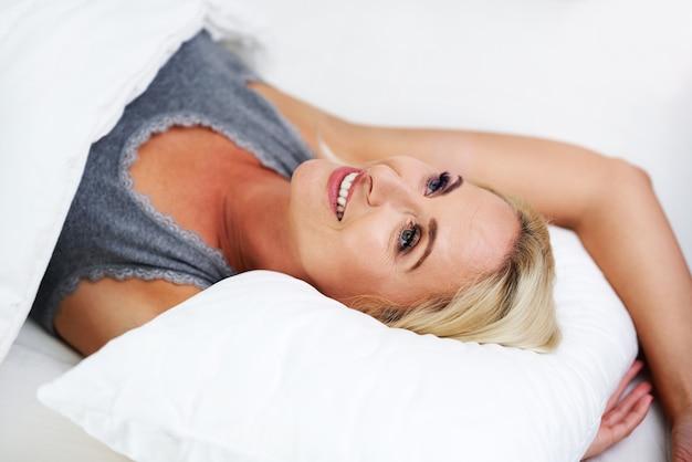 Mulher bonita adulta acordando totalmente descansada.